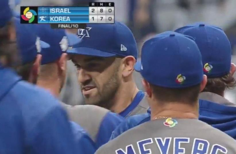 Israel PITCHER Josh Zeid (center) is congratulated by his teammates after he pitched three scoreless innings out of the bullpen yesterday to earn the win in the blue-and-white's 2-1, 10-inning victory over host South Korea to begin play at the World Baseball Classic in Seoul. (photo credit: Courtesy)