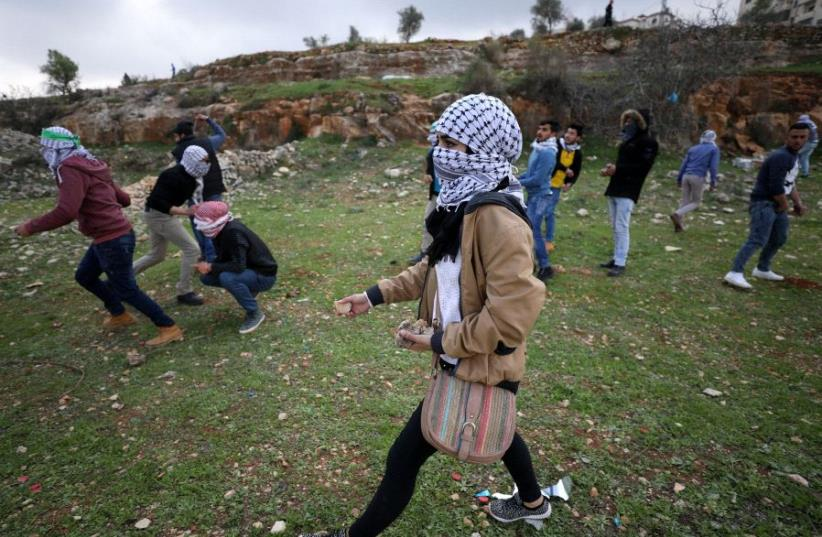 A female Palestinian protester holds stones during clashes with Israeli troops near Israel's Ofer Prison near the West Bank city of Ramallah (photo credit: REUTERS)