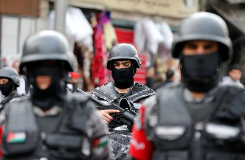 Jordanian policemen stand guard during a rally to support security services after shooting at Karak castle, in Amman, Jordan, December 23, 2016.  (photo credit: REUTERS)
