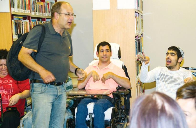 Leslie Henan with members of the Kfar Shmaryahu Social Club for Handicapped Young Adults, where he volunteers (photo credit: MIKE ALTMAN)