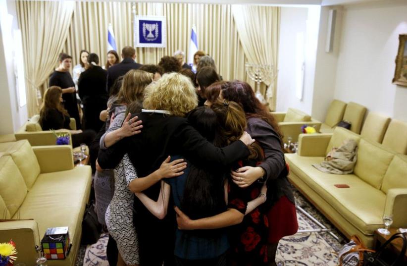 Women who took part in a project ahead of International Women's Day (marked on March 8), hug during a meeting with Nechama Rivlin (not pictured), wife of Israeli President Reuven Rivlin in JerusalemDay (photo credit: REUTERS)