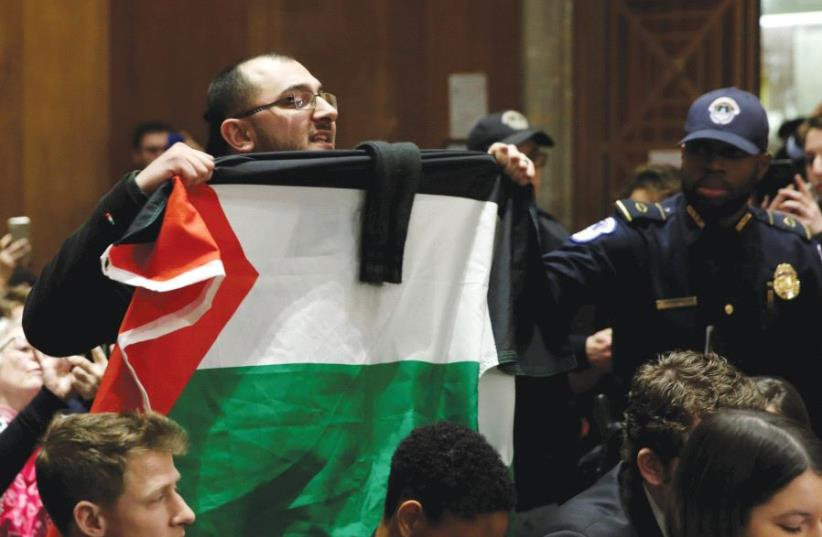 A MAN with a Palestinian flag shouts anti-Israel slogans in Washington. (photo credit: REUTERS)