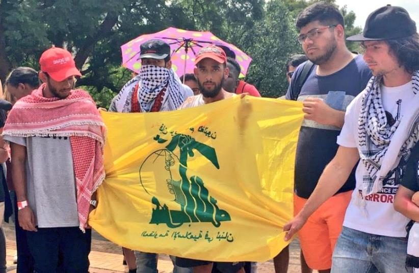 Students hold a Hezbollah flag during a demonstration at Wits University during 'Israeli Apartheid Week' (photo credit: SAUJS)
