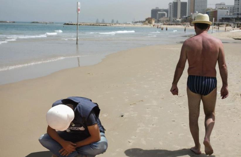 CONFLICT JOURNALIST Bob Worthington III breaks down on Tel Aviv beach as some of the 'natives' stroll by. (photo credit: TAKEN WITHOUT PERMISSION FROM REUTERS)