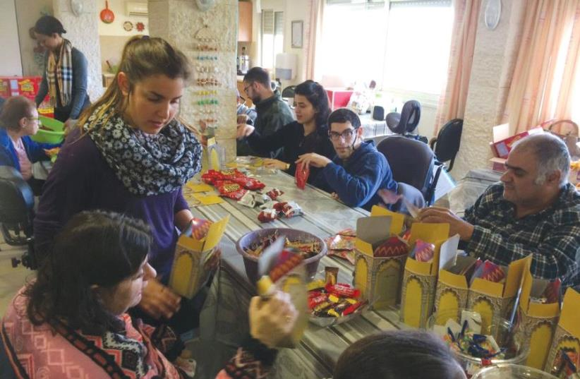 Residents and volunteers prepare some of the 1,500 Purim gifts for Migdal Ha'emek's schoolchildren at the Grabski Center in the North yesterday (photo credit: Courtesy)