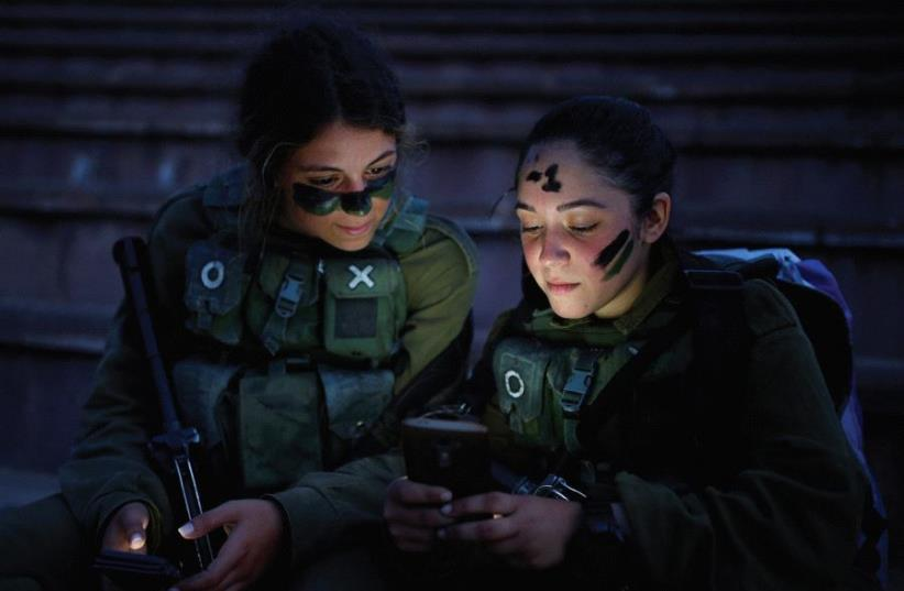 SOLDIERS OF the IDF Search and Rescue brigade rest during a training session in the Ben Shemen forest, near the city of Modi'in last year. (photo credit: REUTERS)