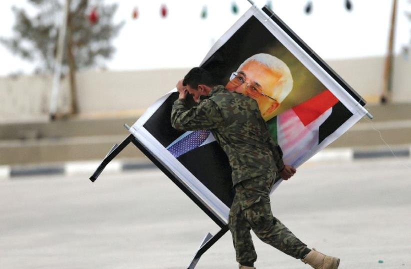 A member of the Palestinian National Security Forces carries a picture of PA President Mahmoud Abbas during a graduation ceremony in Jericho last month (photo credit: REUTERS)