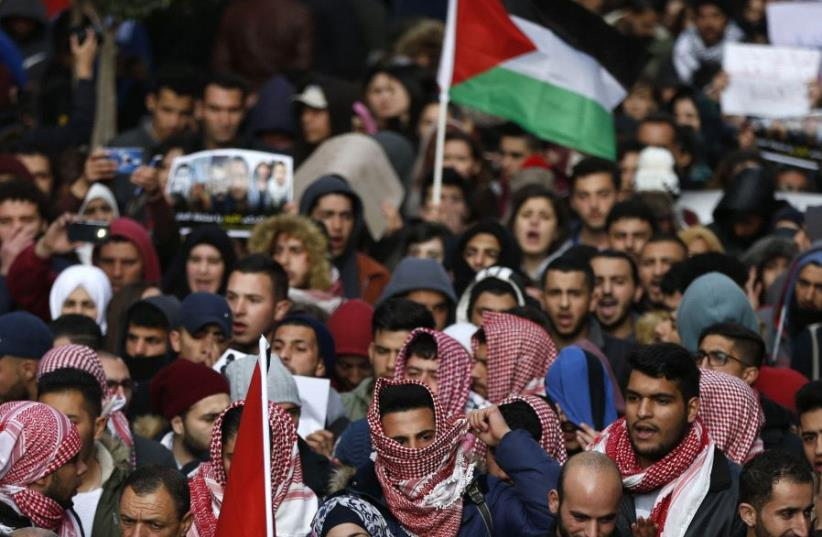 Palestinians demonstrate in the centre of the West Bank city of Ramallah against PA security forces (photo credit: ABBAS MOMANI / AFP)