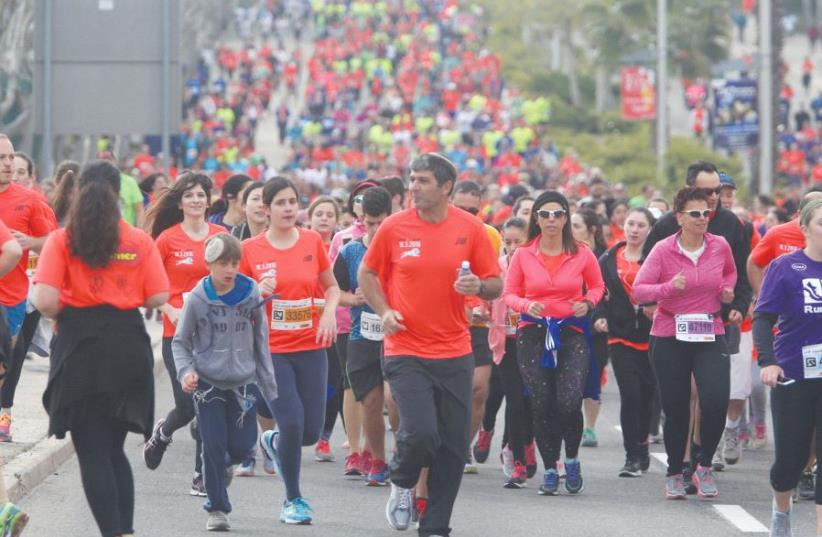 Runners in the 2016 Jerusalem Marathon jog uphill ahead of some 25,000 others who took part in the event (photo credit: MARC ISRAEL SELLEM/THE JERUSALEM POST)
