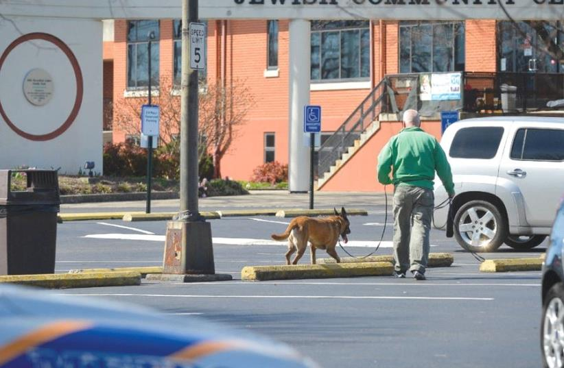 A policeman and a detection dog search for explosives after a bomb threat to the Jewish Community Center in Louisville, Kentucky (photo credit: BRYAN WOOLSTON/REUTERS)