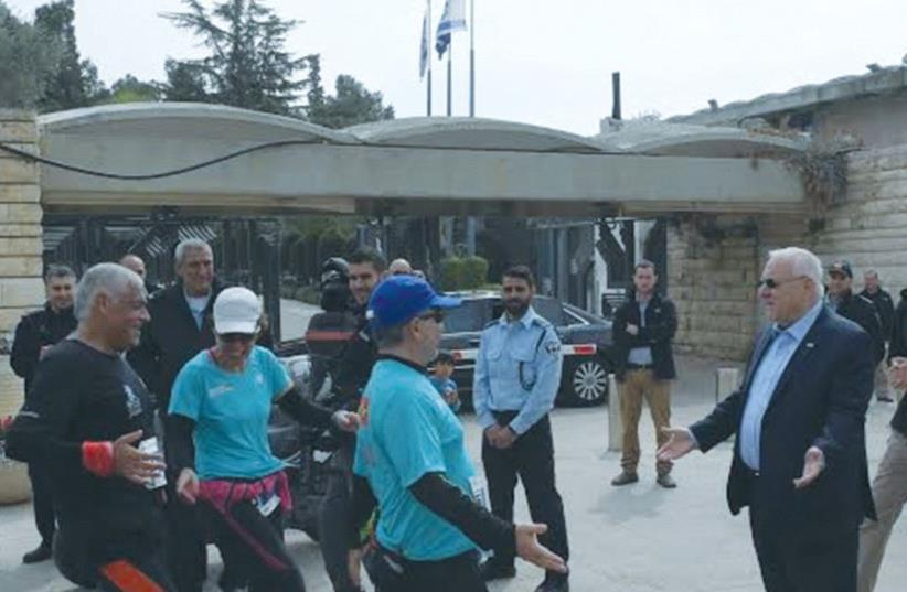 PRESIDENT REUVEN RIVLIN greets runners in the Jerusalem Marathon outside the President's Residence on Friday. (photo credit: GPO)