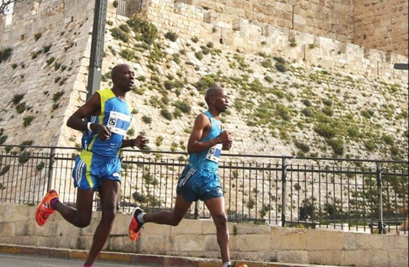 RUNNERS PASS by the walls of the capital's Old City during Friday's seventh annual running of the Jerusalem Marathon. (photo credit: MARC ISRAEL SELLEM)