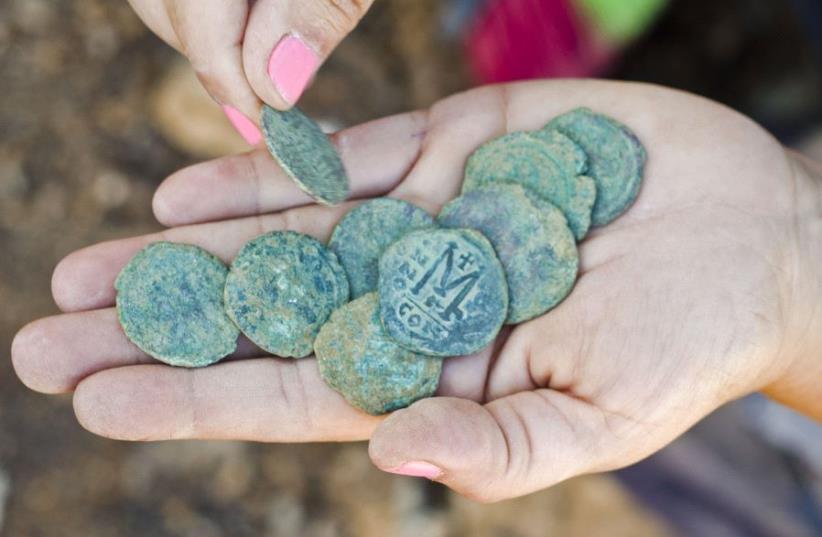 Rare 1,400-year-old bronze Byzantine-era coins found near Jerusalem's Highway 1 (photo credit: YOLI SCHWARTZ/IAA)