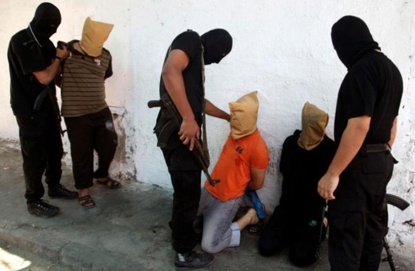 Hamas operatives prepare to execute alleged collaborators in the Gaza Strip (photo credit: REUTERS)