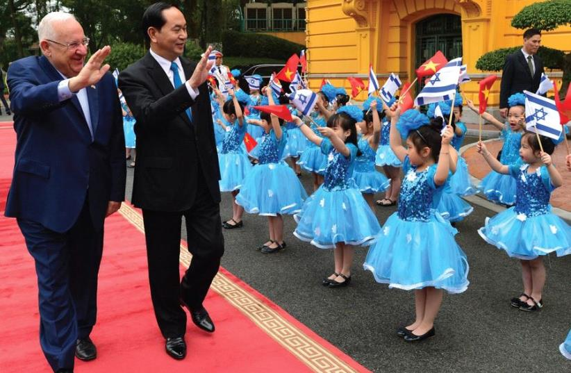 PRESIDENT REUVEN RIVLIN is accompanied by his Vietnamese counterpart, President Tran Dai Quang, yesterday at the Presidential Palace in Hanoi as they review an honor guard including schoolgirls dressed in Israel's national colors. (photo credit: GPO)