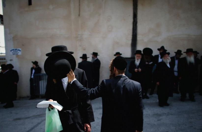 ULTRA-ORTHODOX MEN participate in a 2014 protest outside an IDF recruiting office in Jerusalem (photo credit: REUTERS)
