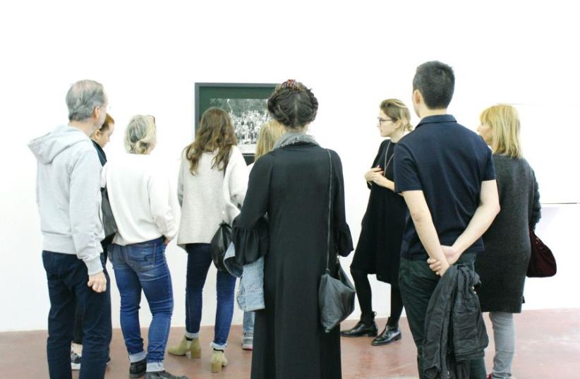 Art adviser Sarah Peguine briefs tour-goers during an art tour in Tel Aviv (photo credit: ALEXIS OSTROBROD/PITAYA WORK)