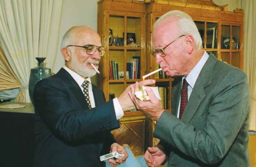 King Hussein of Jordan lights prime minister Yitzhak Rabin's cigarette at the royal residence in Aqaba after signing a peace treaty (photo credit: YAACOV SAAR/GPO)