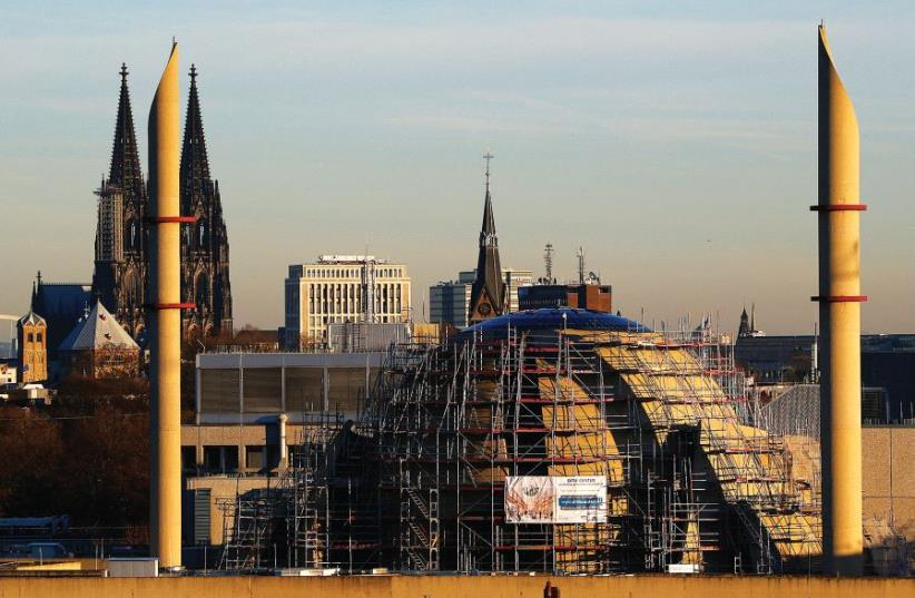 THE COLOGNE CATHEDRAL is seen next to the two minarets of the new Cologne Central Mosque. (photo credit: REUTERS)
