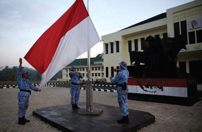 PARTICIPANTS RAISE an Indonesian flag at a training center in Rumpin, Indonesia, last June. (photo credit: REUTERS)