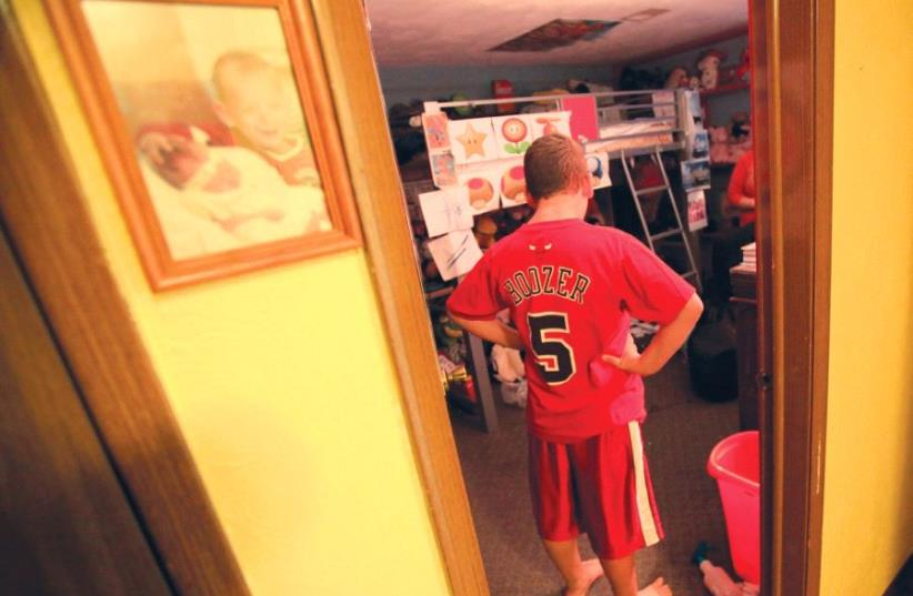 A boy with autism stands in his room (photo credit: REUTERS)