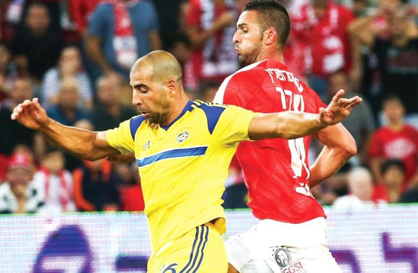 Maccabi Tel Aviv defender Tal Ben-Haim (left) and Hapoel Beersheba striker Ben Sahar (right) are set to clash once more on Saturday when the Premier League's top two teams meet at Turner Stadium. (photo credit: DANNY MARON)