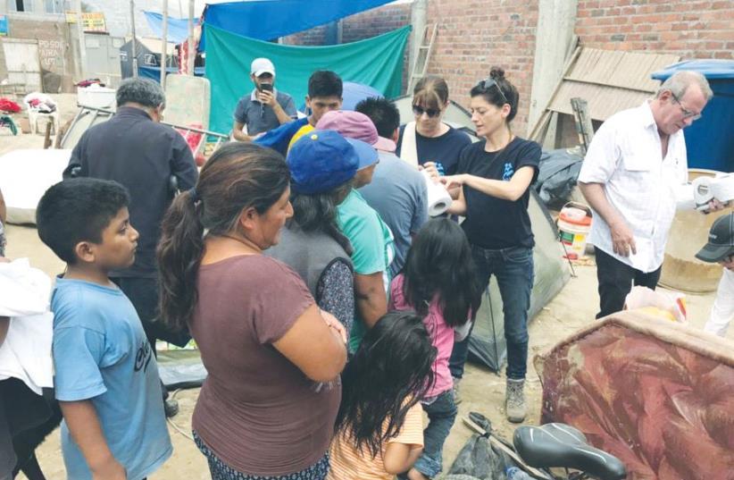 ISRAAID STAFF MEMBERS assist displaced residents in Lima last Friday. (photo credit: ISRAAID)