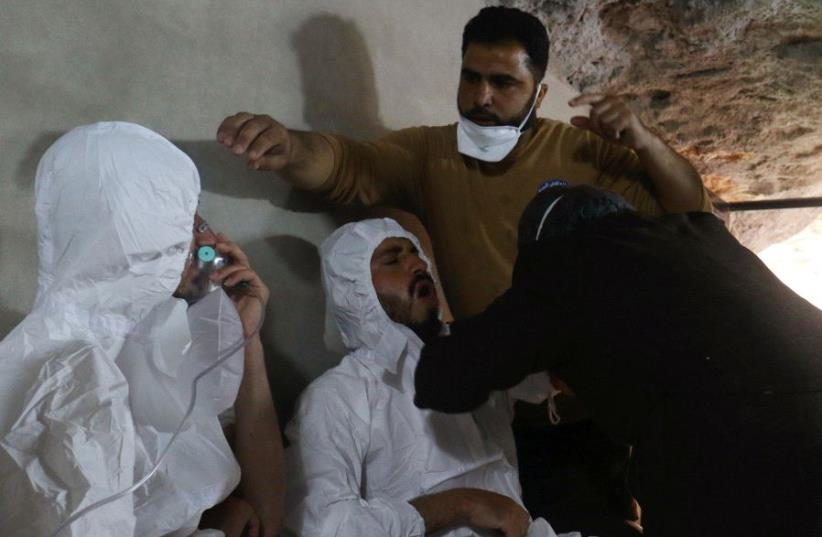 A man breathes through an oxygen mask as another one receives treatments, after what rescue workers described as a suspected gas attack in the town of Khan Sheikhoun in rebel-held Idlib, Syria April 4, 2017 (photo credit: REUTERS)