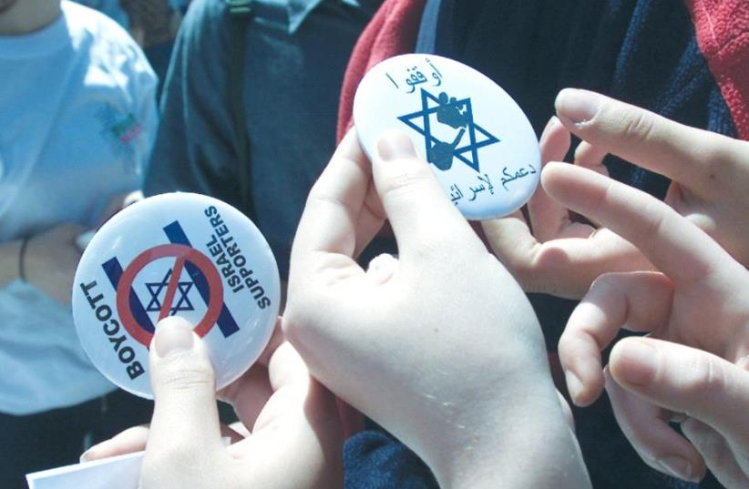 LEBANESE STUDENTS hand out buttons encouraging a boycott of Israel. (photo credit: REUTERS)