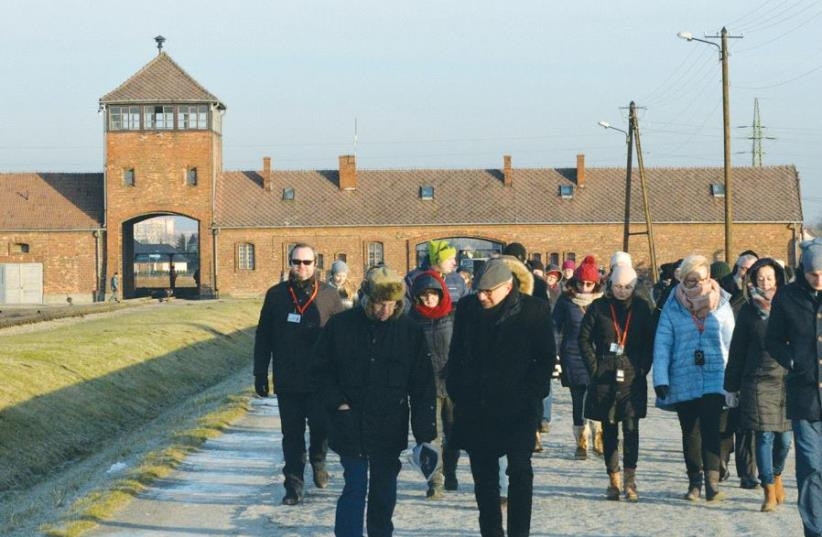 AMUD AISH MEMORIAL MUSEUM lecturer Rabbi Aubrey Hirsch and Amud Aish chief curator Dr. Henri Lustiger Thaler lead a docent training group, with the main entrance to Auschwitz II (Birkenau) in the background (photo credit: ABMM)