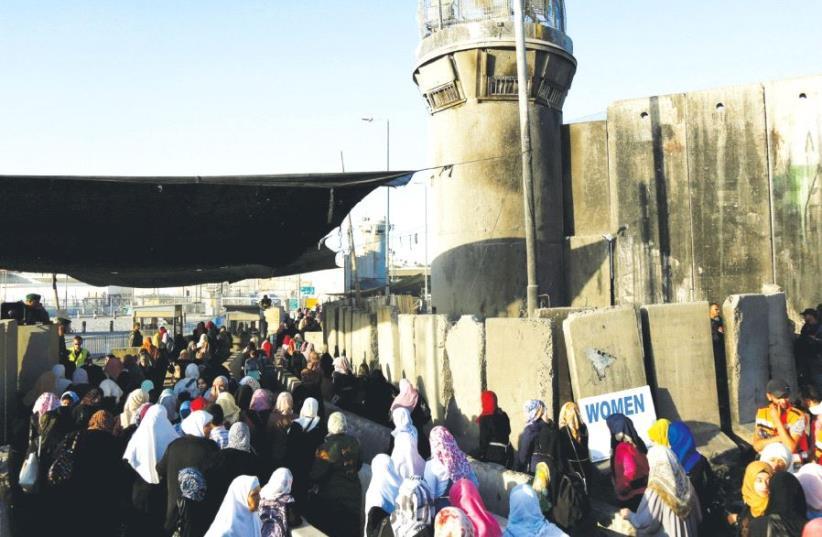 Palestinians wait to cross through Kalandiya checkpoint into Israel, near Ramallah. (photo credit: REUTERS)