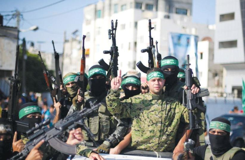 Freed Palestinian prisoner Mohammed al-Bashiti, who served 12 years in an Israeli jail after he was convicted of being a member of Hamas's armed wing, gestures as he holds a weapon in a pickup truck with Hamas militants upon his release, in the southern Gaza Strip, last year (photo credit: REUTERS)