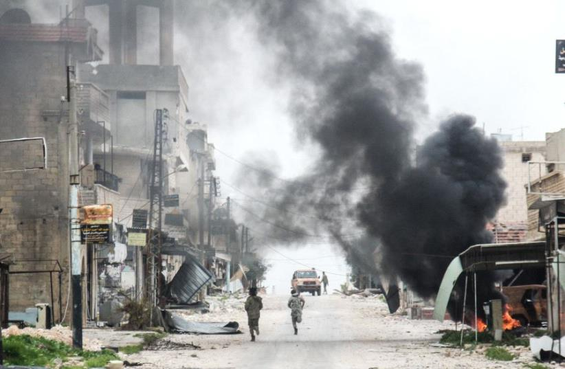 A picture taken on March 22, 2017 in the Syrian town of Tayyibat al-Imam in the countryside of the central province of Aleppo, shows fighters running amdist destruction down a street past a rising plume of smoke from a burning tire meant to disrupt warplanes (photo credit: OMAR HAJ KADOUR / AFP)