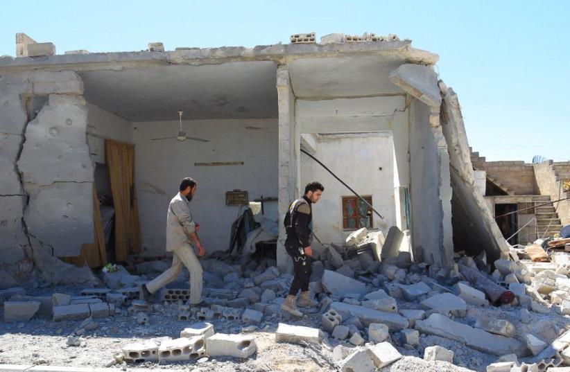 SYRIAN CIVIL DEFENSE members inspect the damage at a site hit by air strikes on Tuesday, in the town of Khan Sheikhoun in rebel-held Idlib (photo credit: REUTERS)