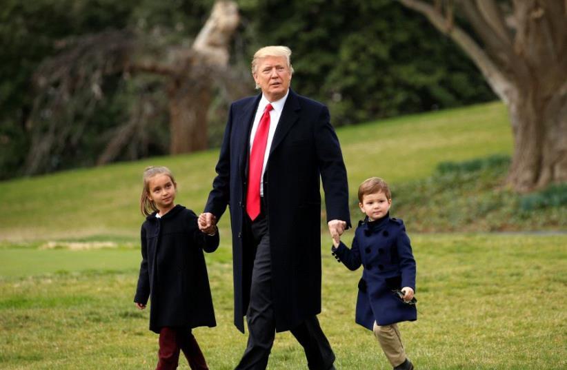 U.S. President Donald Trump holds hands with grandchildren Arabella and Joseph Kushner (photo credit: KEVIN LAMARQUE/REUTERS)