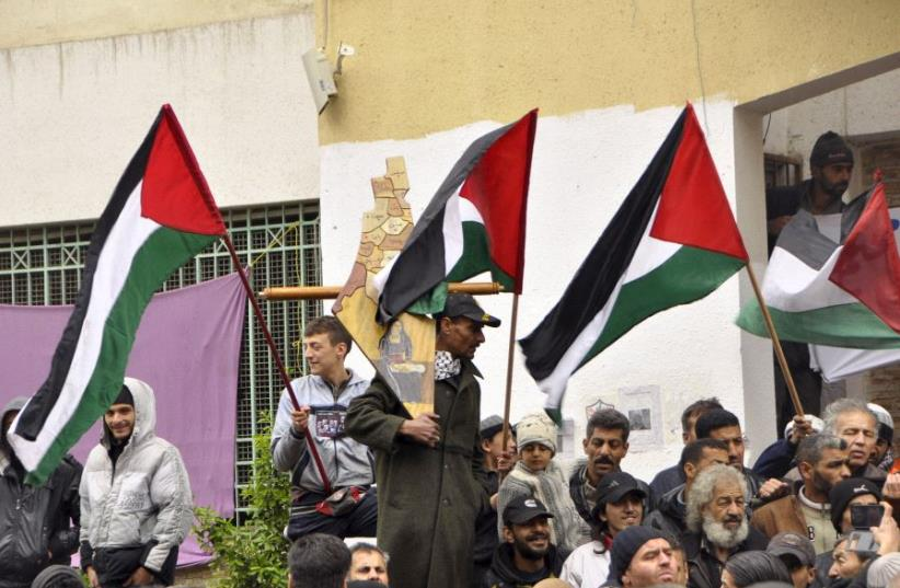 Palestinian residents of the Yarmouk refugee camp in the Damascus district of Syria wave their national flags as they take part in a protest expressing their will to stay inside the camp. (photo credit: REUTERS)