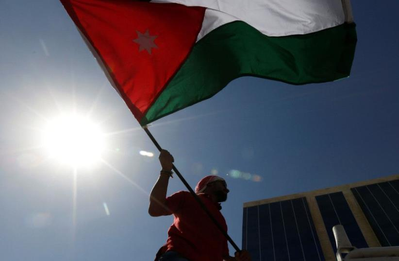 A Jordanian protester holds a Jordanian national flag (photo credit: REUTERS)