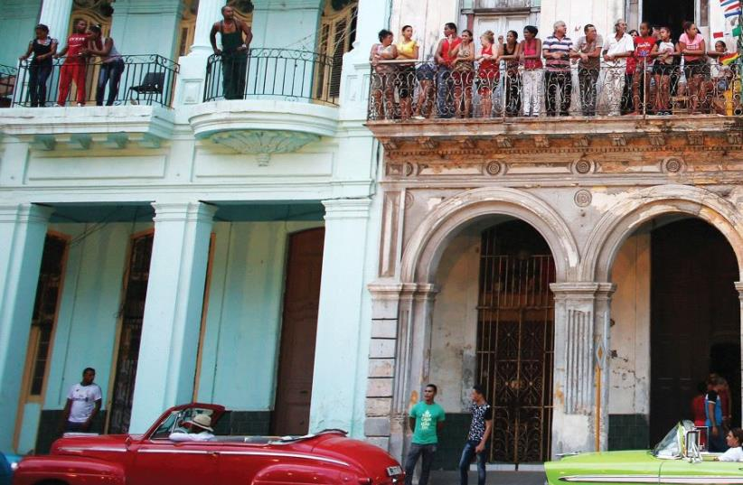 PEOPLE STAND on balconies on Paseo del Prado street in Havana, Cuba. (photo credit: REUTERS)