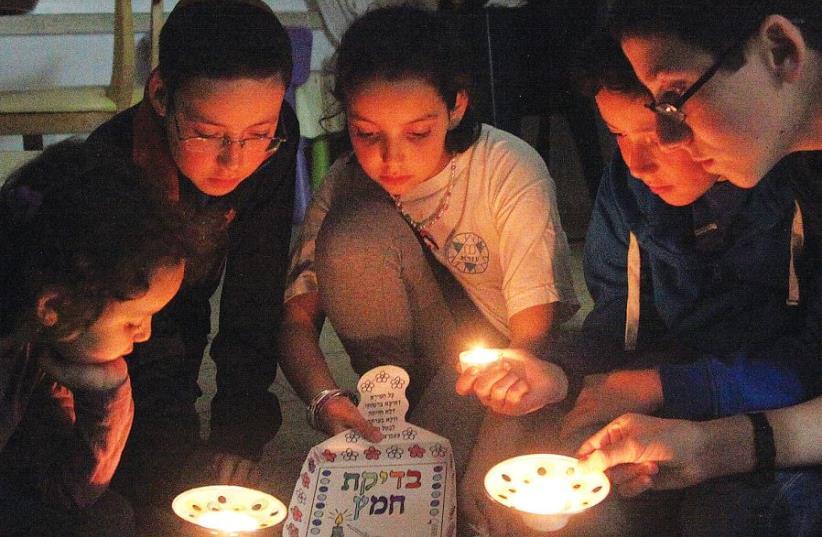 MEMBERS OF the Nataf family take part in 'bedikat hametz' ritual in Jerusalem. (photo credit: MARC ISRAEL SELLEM)