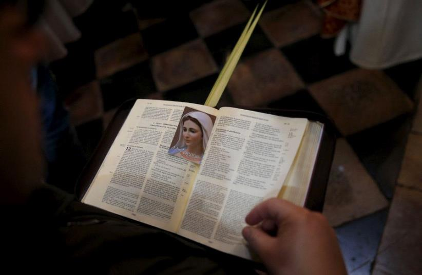 A worshipper holds an opened Bible during a Palm Sunday procession at the Church of the Holy Sepulchre in Jerusalem's Old City. (photo credit: REUTERS)