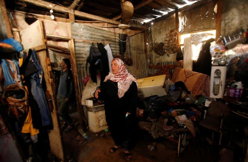 A Palestinian woman inspects her shelter that was flooded during a rainstorm, in the northern Gaza Strip. (photo credit: REUTERS)