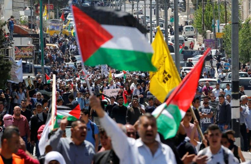 Palestinians take part in a protest in solidarity with Palestinian prisoners held by Israel, in the West Bank town of Bethlehem April 17, 2017 (photo credit: REUTERS/AMMAR AWAD)