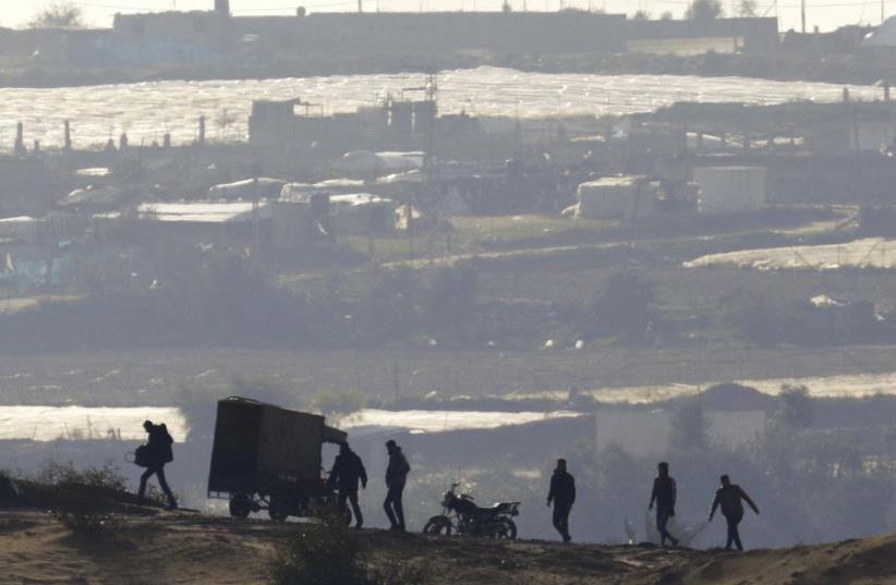PALESTINIANS WALK near the Israel-Gaza border inside Gaza, where Hamas still holds Israeli citizens. (photo credit: REUTERS)