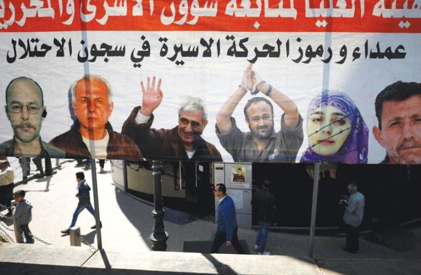People in Ramallah walk past a poster depicting Palestinian prisoners held in Israeli jails (photo credit: REUTERS)