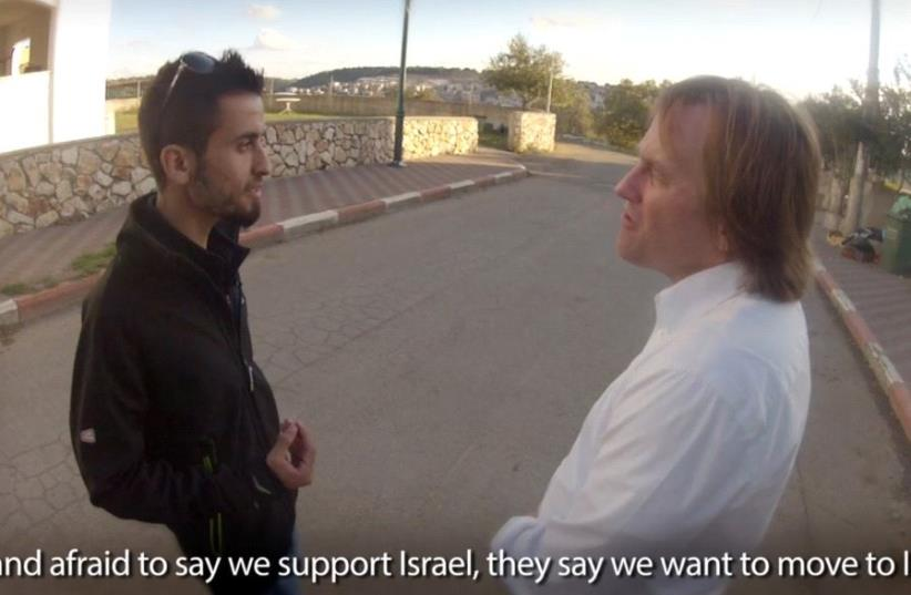 A screenshot from the film 'Boycott This!' showing comedian Brad Stine speaking with a Palestinian in the West Bank. (PTJN) (photo credit: PTJN)