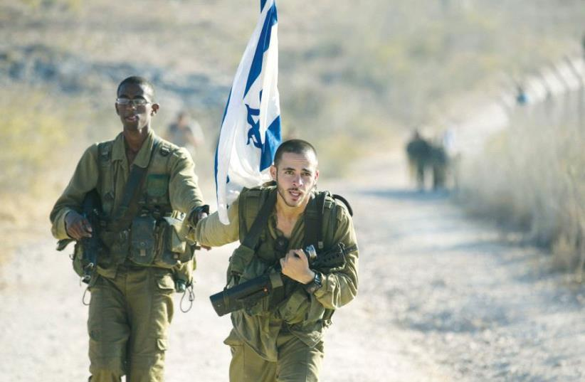 A soldier from the Golani Brigade holds a comrade's hand as he helps him during a 70-kilometre march, marking the completion of their advanced training, at the end of which they receive their brown beret, in 2014 (photo credit: REUTERS)