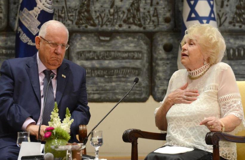 President Reuven Rivlin speaks to Holocaust survivor Miriam Eshel. (photo credit: MARK NEYMAN / GPO)