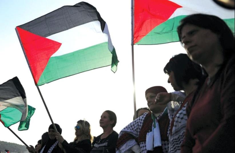 Israeli Arabs raise Palestinian flags at a Land Day rally, March 30 (photo credit: REUTERS)