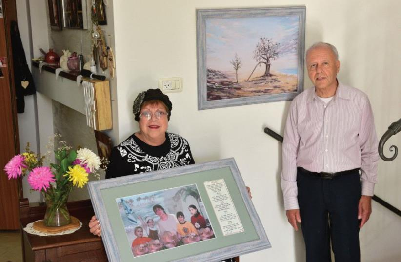 In their Ashkelon home, Suzy and Momi Malka show a picture of their daughter Tali and four granddaughters (photo credit: ZION BARON)