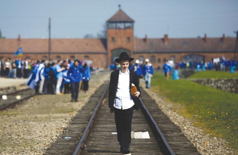 A man walks on the railway tracks in the former Nazi death camp of Auschwitz-Birkenau (photo credit: REUTERS)